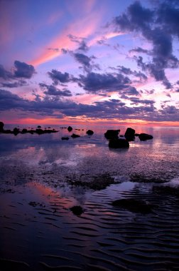 A stunning pink, purple and blue sunset over sand flats and rock outcrops on Great Island, Cape Cod, Massachusetts
