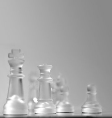 Shallow depth of field view of a chess board centered around the white queen, other pieces in soft focus in smooth grey background. Plenty of copy-space for presentation and slides