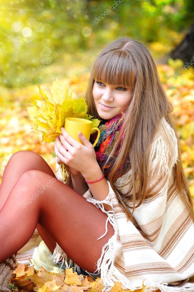Young beautiful woman that holds the cup of tea in hands on a background autumn leaves