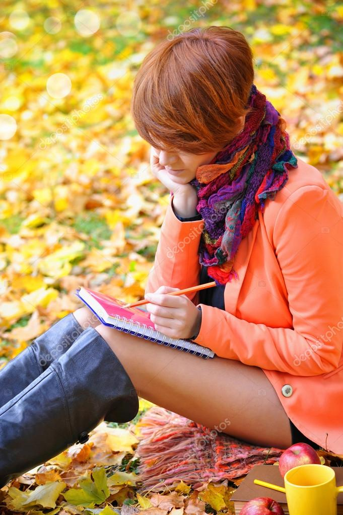 Red-haired student girl with notebook on a background autumn leaves