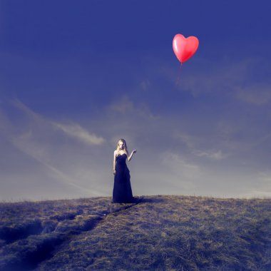 Elegant Blonde Girl Letting Go Off a Heart Shaped Balloon