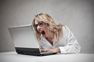 Business woman screaming against her laptop