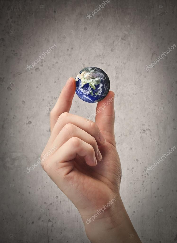 Small ball with the world on it held by a man's hand