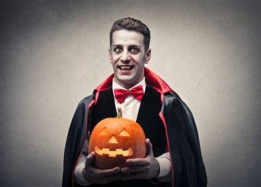 Vampire holding a Halloween pumpkin