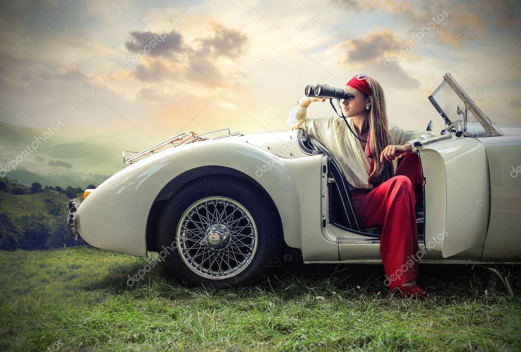 Beautiful fashion woman looking through a binoculars
