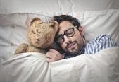 Muž, který držel jeho teddy do postele