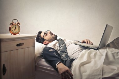 Businessman sleeping into bed with his laptop