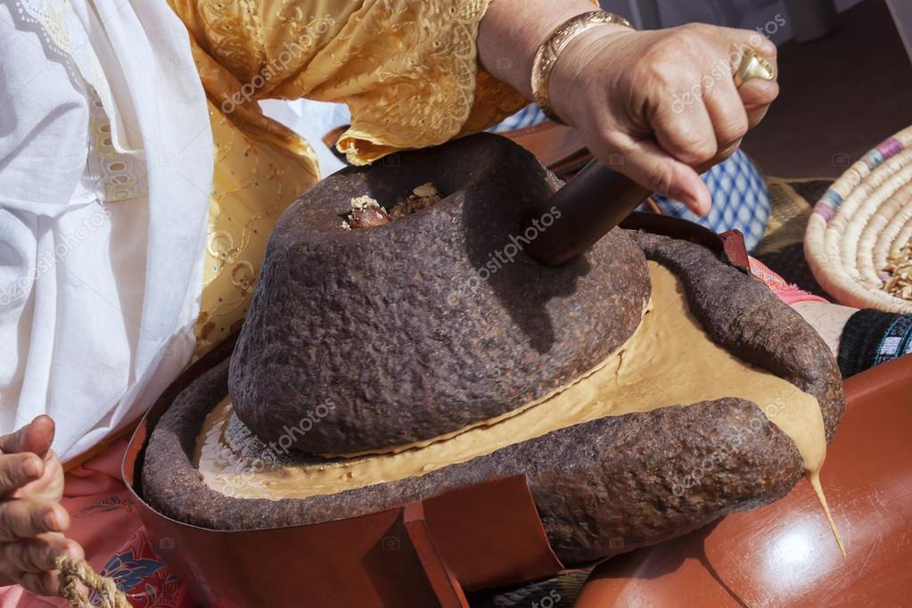 Moroccan woman grinding argan kernels traditionally with a mills
