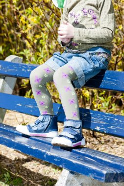 close up of little girl sitting on bench