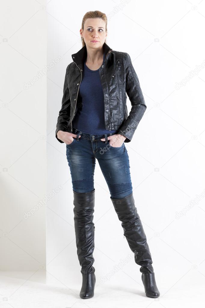 Giovane donna in gilet di jeans, stivali neri e cappello in pelle scamosciata marrone è seduto su una cima e guarda verso il basso. Colpo di studio