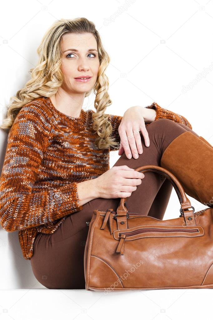 e5110062b Retrato de mujer que se sienta vistiendo ropas marrones y botas con un —  Foto de