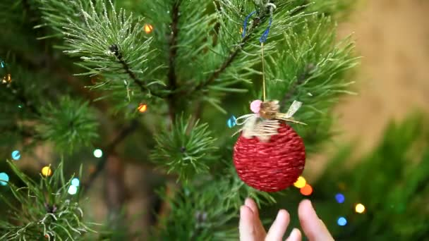 Female hand decorating Christmas tree with toys