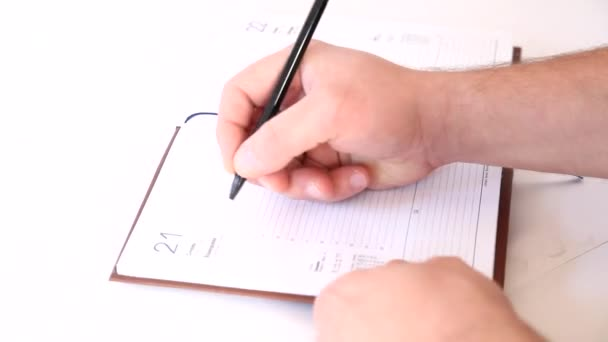 Man writing information in business agenda book