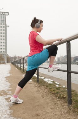 Young woman doing warm-up exercises for jogging
