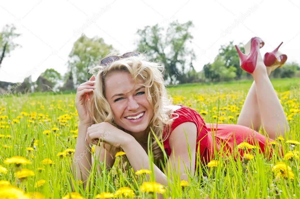 Happy woman lying down on dandelion field