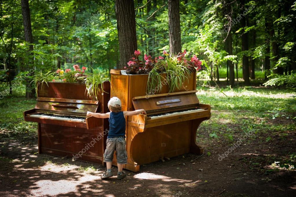 Little boy is playing on two pianos in the park