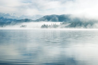 Heavy fog in the early morning on a mountain lake