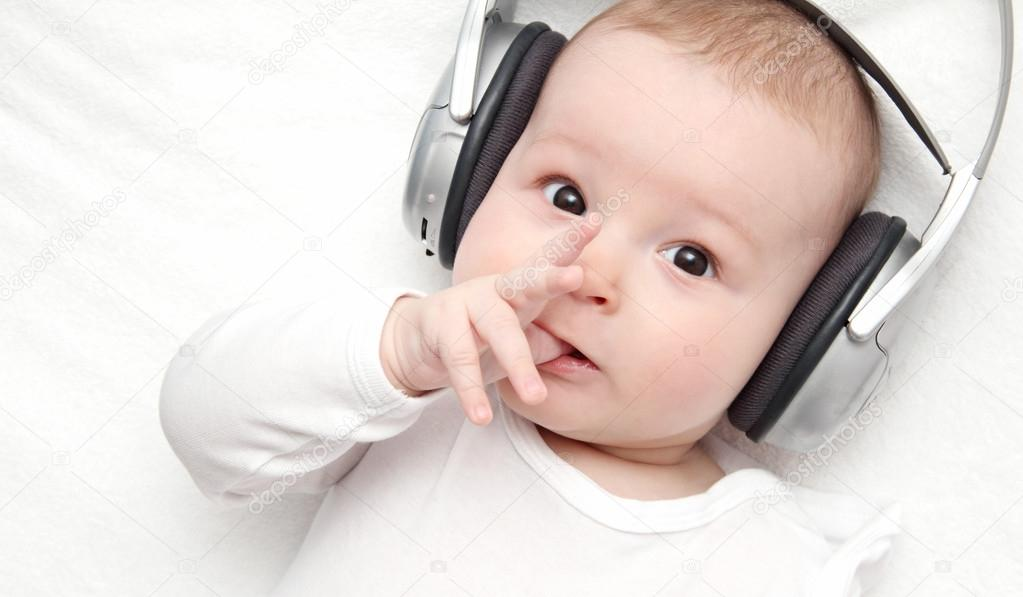 Baby boy with headphone lies on back