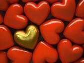 Fotografie rote Herzen und ein goldenes Herz isoliert auf dem Hintergrund