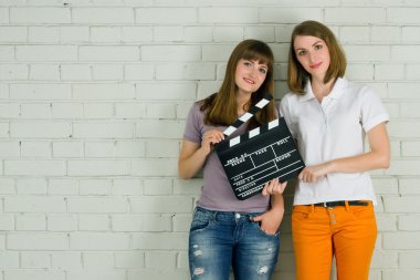 Young smiling girls with a clapboard