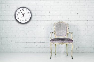 Vintage chair against white brick wall with clock