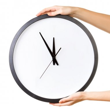 Woman holding a big clock isolated on a white background.