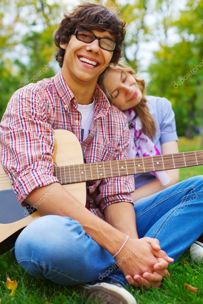 Cheerful teenage couple with guitar in park