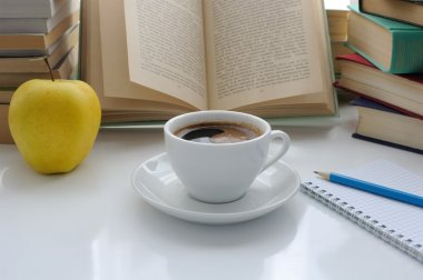A cup of coffee and an apple on a table among books