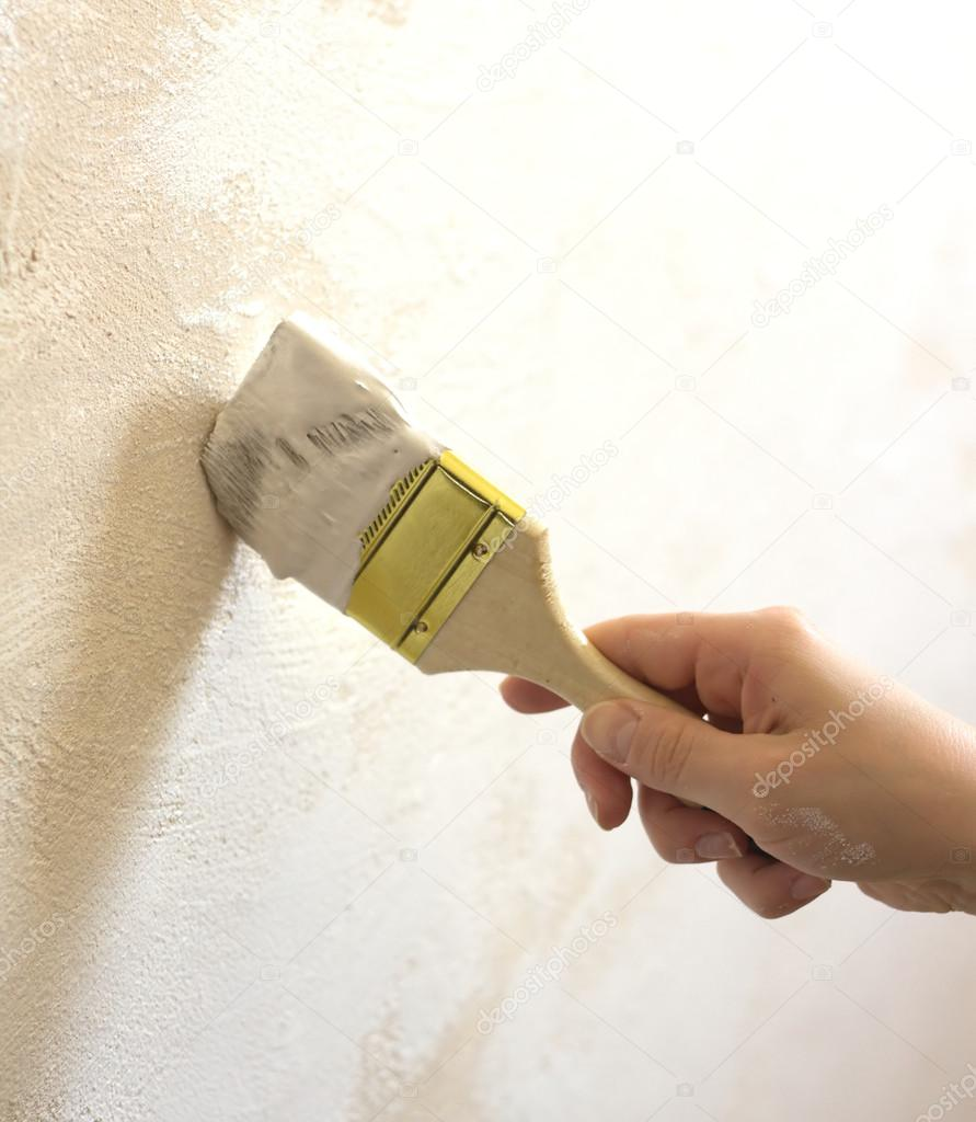 Woman's hand with brush painted wall
