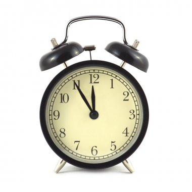 Alarm clock in black case and beige clockface isolated close up