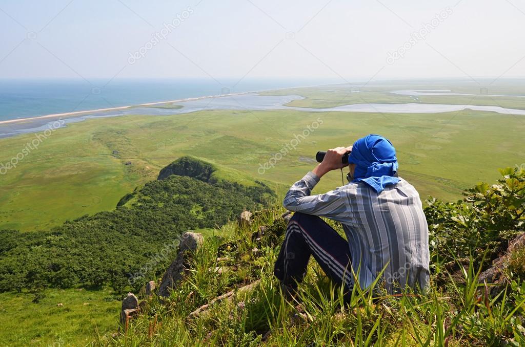 Man looking in binoculars, the border of Russia with North Korea