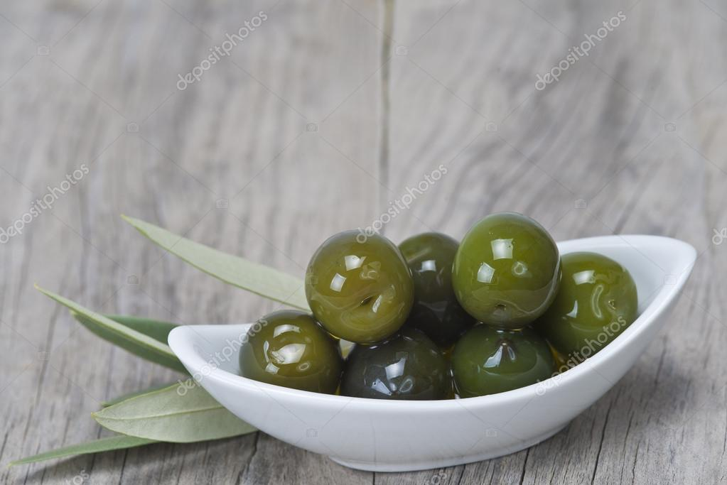 Saucer with olives on a wooden surface