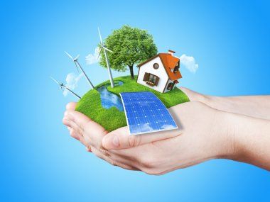 Hands holding clear green meadow with sun battery block, wind mill turbines and countryside house