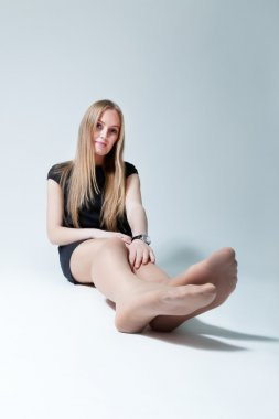 Pretty lady sitting on the floor. Wearing fashionable dress and