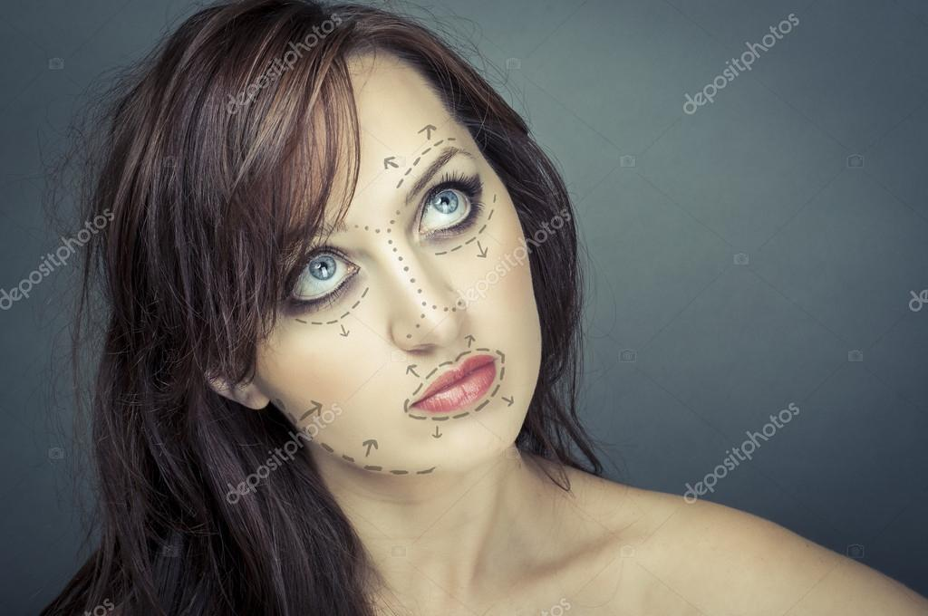 Beautiful young woman with perforation lines on her face before plastic surgery operation