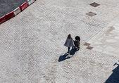 žena s kočárek na šedém asfaltu