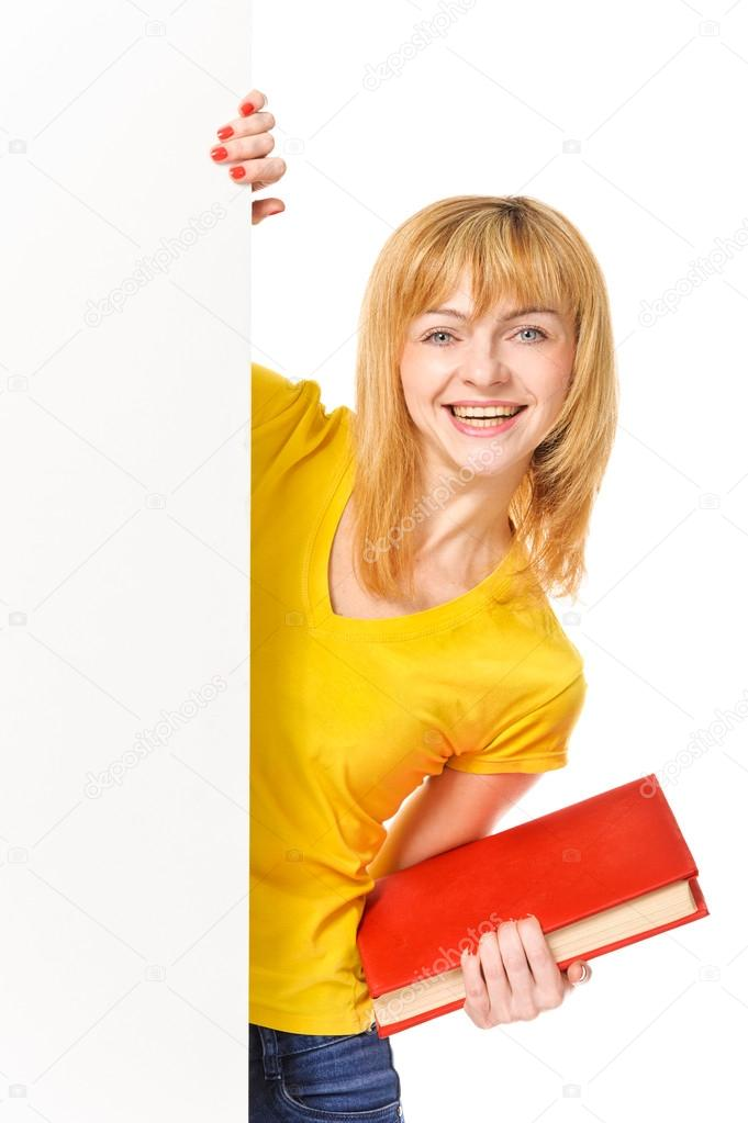 Young student with book standing behind white board. Isolated on