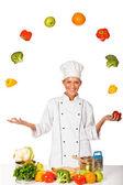 Frau Koch Jonglieren mit frischem Gemüse. isoliert