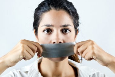 Woman with mouth covered with tape. Concept of forbidden opinion