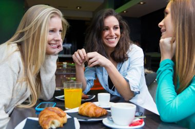 three young friends having breakfast on a morning shopping in th