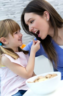 Child eating cereals with her mom in the kitchen