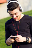 Fotografie mladý chlapec, poslech hudby s smartphone v ulici