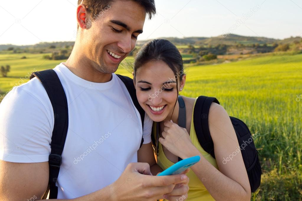 young couple outdoors looking at the mobile phone