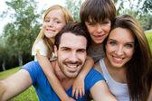 Boldog fiatal család vesz neki smartphone selfies a par