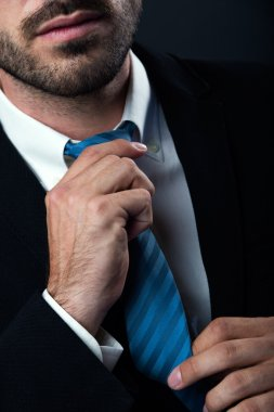 Businessman without face straightens tie himself. Isolated on black.