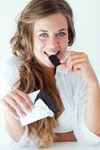 junge Frau in Unterwäsche beim Schokoladenessen. isoliert auf weiß.
