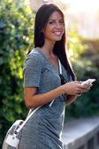 Fotografie usmívající se krásná žena textilie s její telefon v zahradě