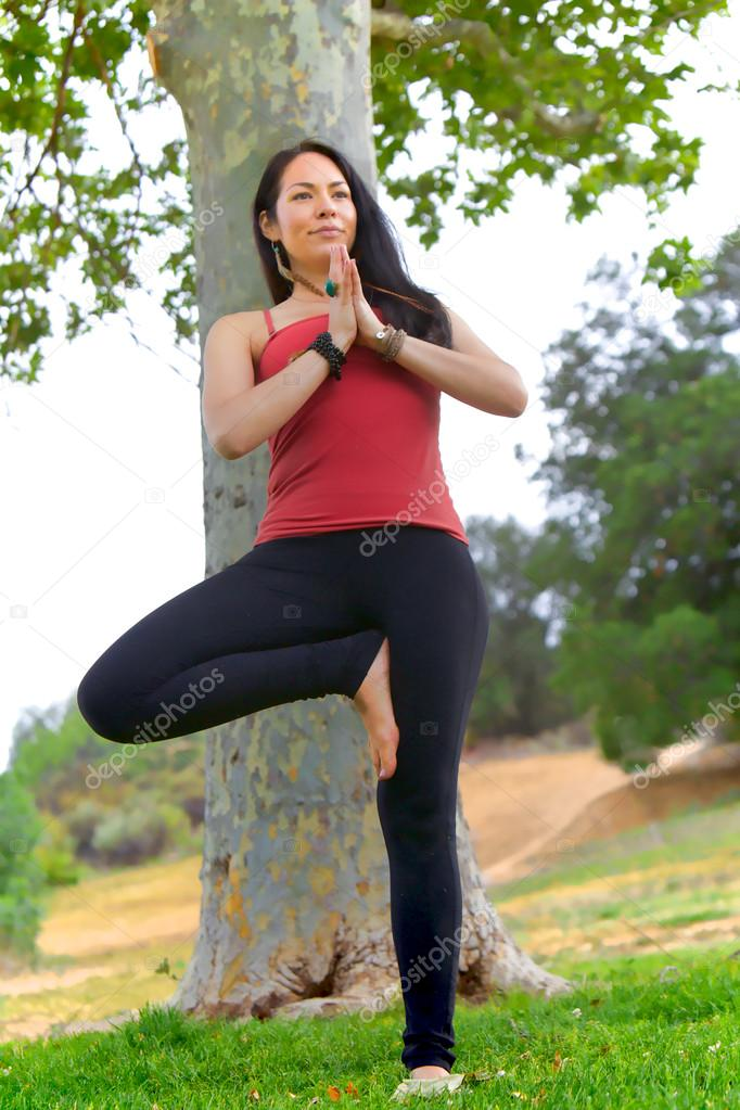Woman Stands in Front of Tree Performing Yoga Tree Pose