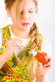 Mladá dívka malba velikonoční vajíčko červený