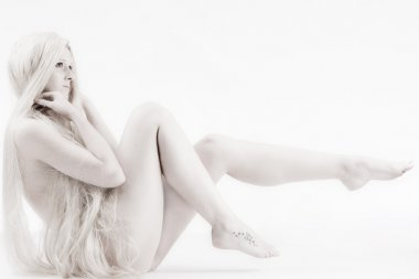 Long blond haired artistic beauty pulling up her legs